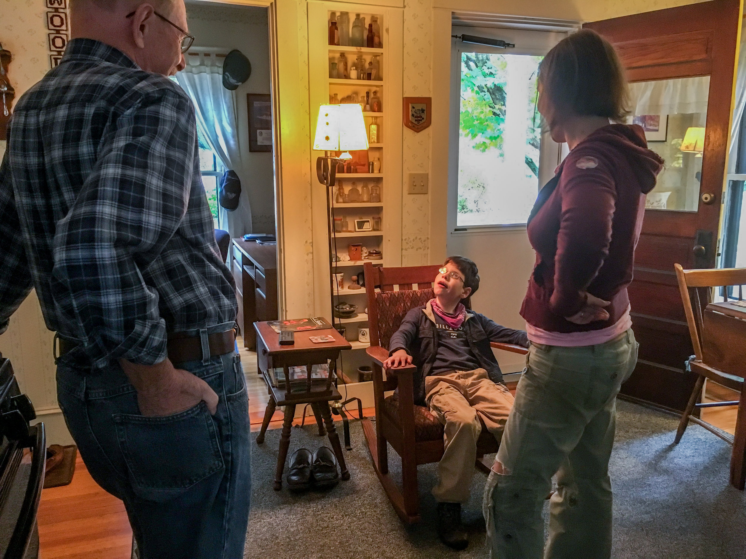 Calvin sits in a rocking chair eating a piece of chocolate at a neighbor's house on October 8, 2017 in Brunswick, Maine. Since reducing his benzo dose and adding cannabis to his treatment routine, Christy says Calvin has become calmer, more mobile, and easier to take places. Often they walk down the block to check on their elderly widowed neighbor Woody.