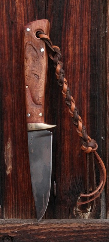 Custom handmade drop point knife with a hand carved knife handle. The wolf.