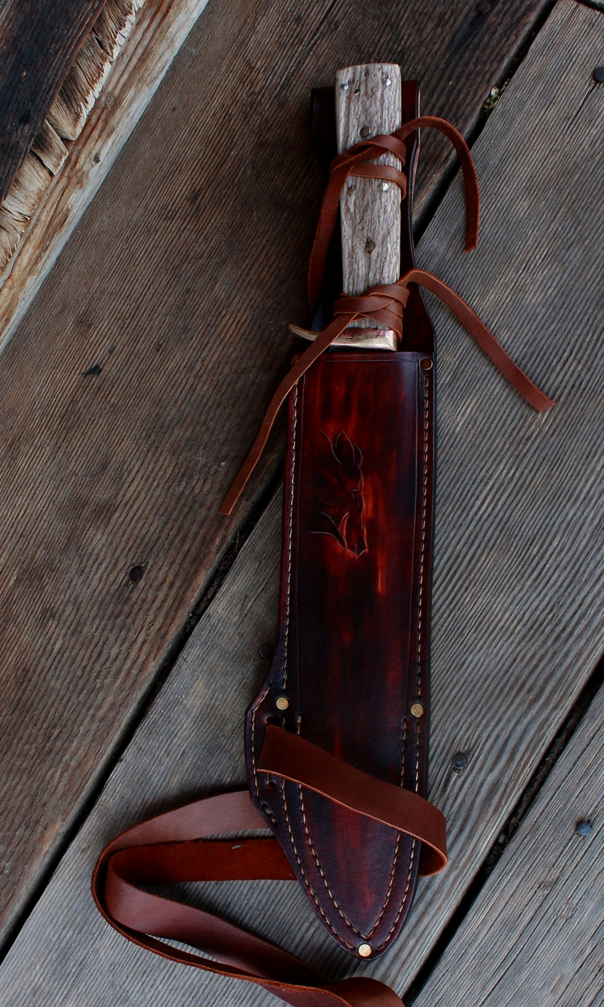 A hand forged 10 inch edge Boar survival knife with leather tie security. We double stitch all of our bush craft and survival sheaths now.