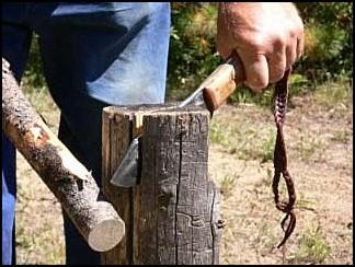 Bushcraft knife splitting wood with a baton.