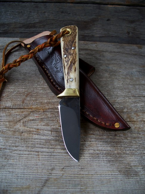 Custom drop point hunting knife. Equipped with an angled belt loop.