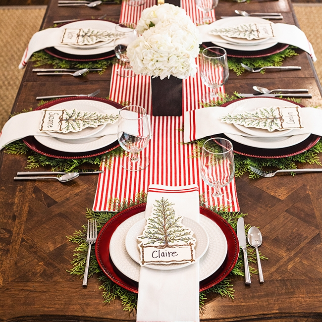 Oh What Fun - Tablescape Includes:Table Runner (Red/White Stripe/The North Pole Reversible), Pine Tree Charger, Red Charger, Plate, Napkin, Place Card$14.99 per tablescapeAnd Oh What Fun your guests will have with this table setting! A reversible table runner allows you to choose your look. Pine tree accessories compliment the red accent color for the perfect holiday tablescape that will create a reminiscent feel for all ages!