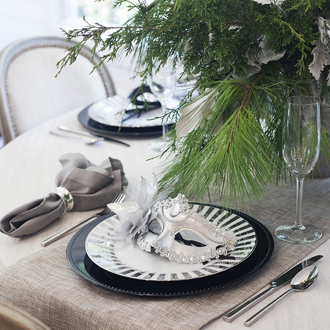 Midnight Masquerade - Table Setting Includes:Platinum Table Runner, Charger, Plate, Napkin, Napkin Ring, Mask (To Keep)$14.99 per table settingThis eye-catching table setting will be the talk of the party. Platinum, grays, and sparkling silver create a marvelous way to ring in the New Year! The mask is a fun favor for each guest to keep!