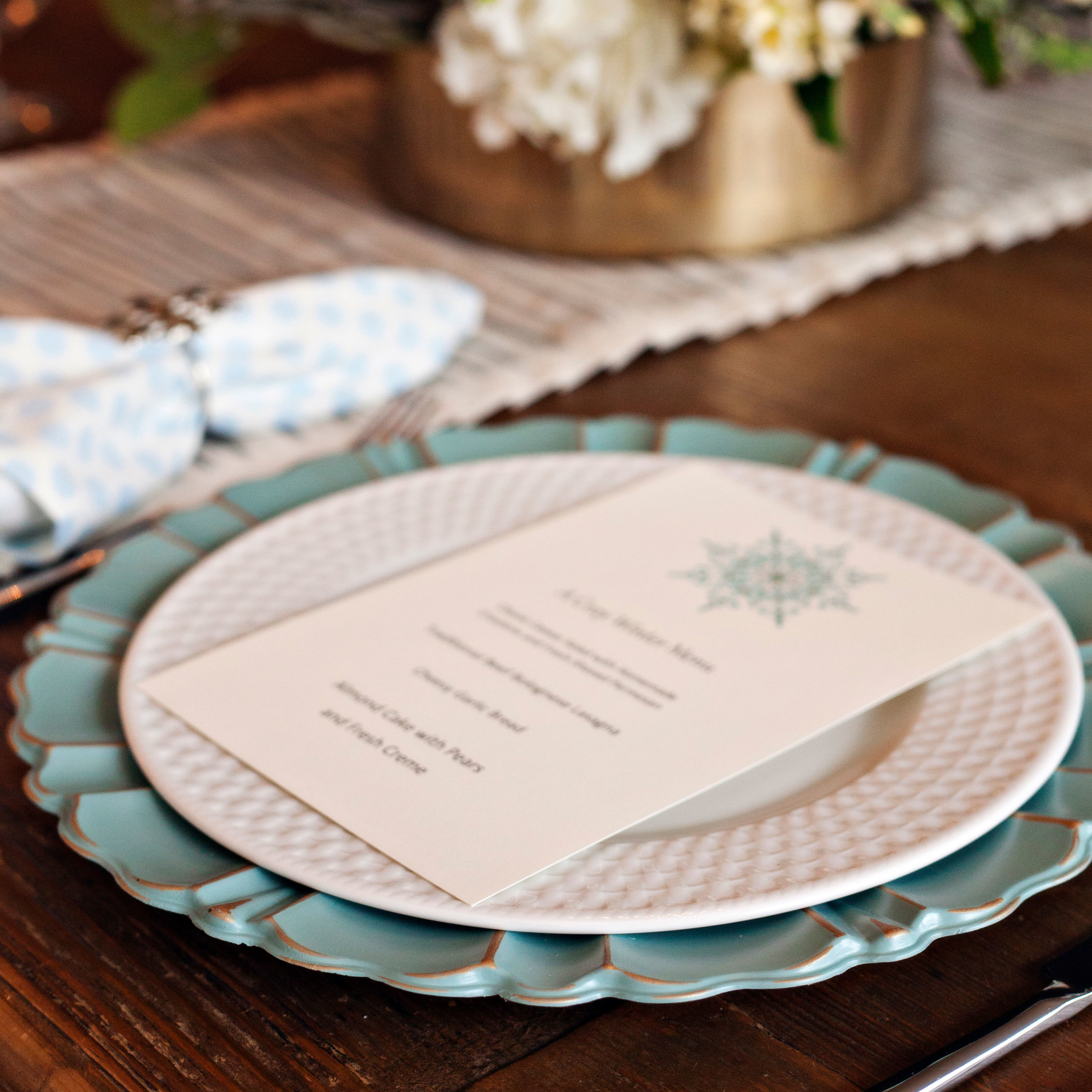 A Cozy Winter Meal - Tablescape Includes:Striped Table Runner, Blue Hued Charger, Plate, Polka Dot Napkin, Snowflake Napkin Ring, and Snowflake Printed Menu (Printed prior to delivery, if desired)$14.99 per tablescapeYour guests will be whisked away to a cozy winter meal with this inviting table setting! Snowflakes and polka dots add whimsical charm to your table, with an added treat for your guests to anticipate your planned menu as they sit down to dine.