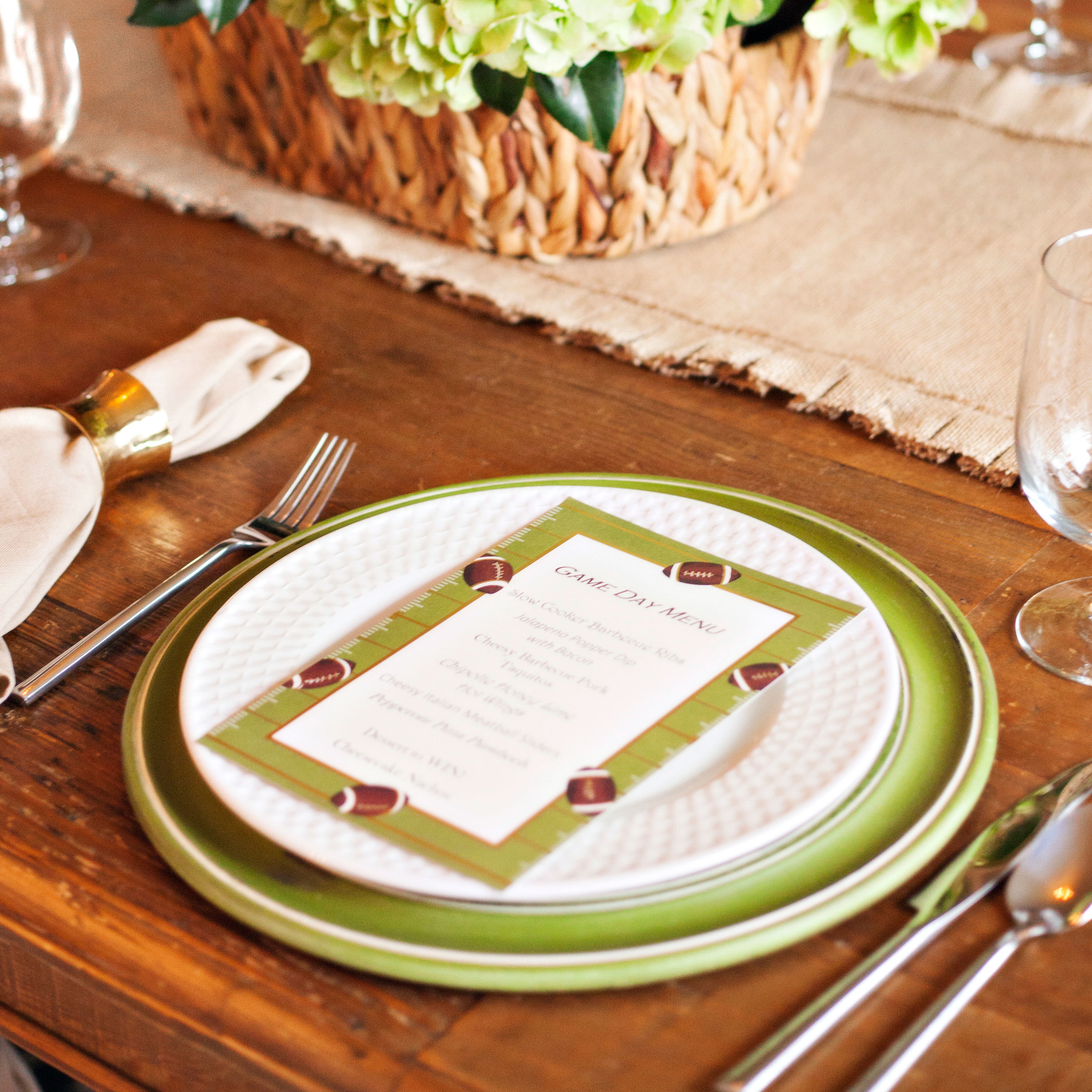 Game Day - Tablescape Includes:Burlap Table Runner, Green Charger, Plate, Napkin, Gold Napkin Ring, Game Day Menu (Printed prior to delivery, if desired)$14.99 per tablescapeBring your favorite sport to your tablescape with this fun inspired table setting. The burlap runner, paired with a football theme, will treat your guests to an evening of entertainment as you enjoy dinner while rooting for their team!