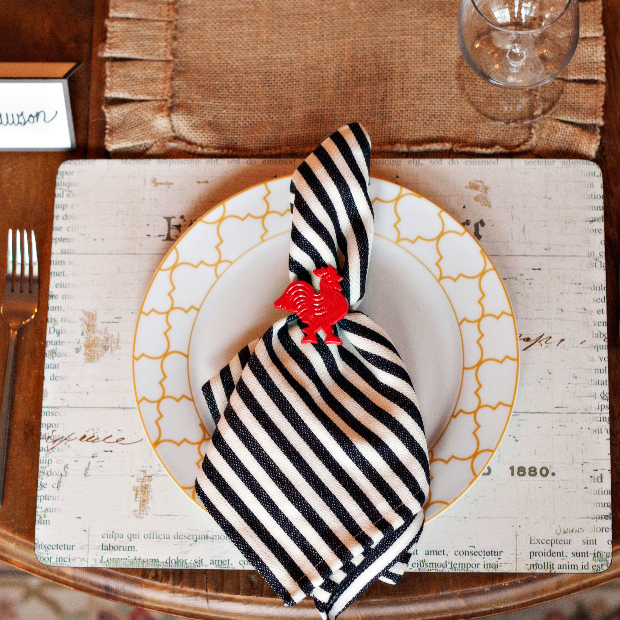 Red Rooster - Tablescape Includes:Table Runner, 'Fresh Eggs' Hardboard Placemat, Plate, Black/Cream Striped Napkin, Red Rooster Napkin Ring, and Place Card$14.99 per tablescapeYour Red Rooster Table Setting will surely make your guests smile as they sit down to enjoy your time together! Burlap, cream and a pop of red create a lovely festive feel. This tablescape has everything needed to leave your guests feeling like 'Life is good in the coop'.