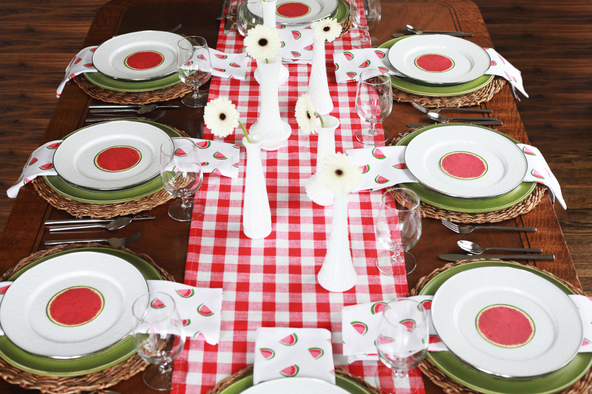 Hello Summer - Tablescape Includes:Red and white checkered table runner, rattan charger, plate, green charger, watermelon themed napkin, silver rimmed plate, watermelon place card$14.99 per TablescapeWhimsical watermelons dancing on the napkins is sure to launch summertime at your next gathering! This refreshing tablescape is fun and cheerful; perfect for spring and summer!