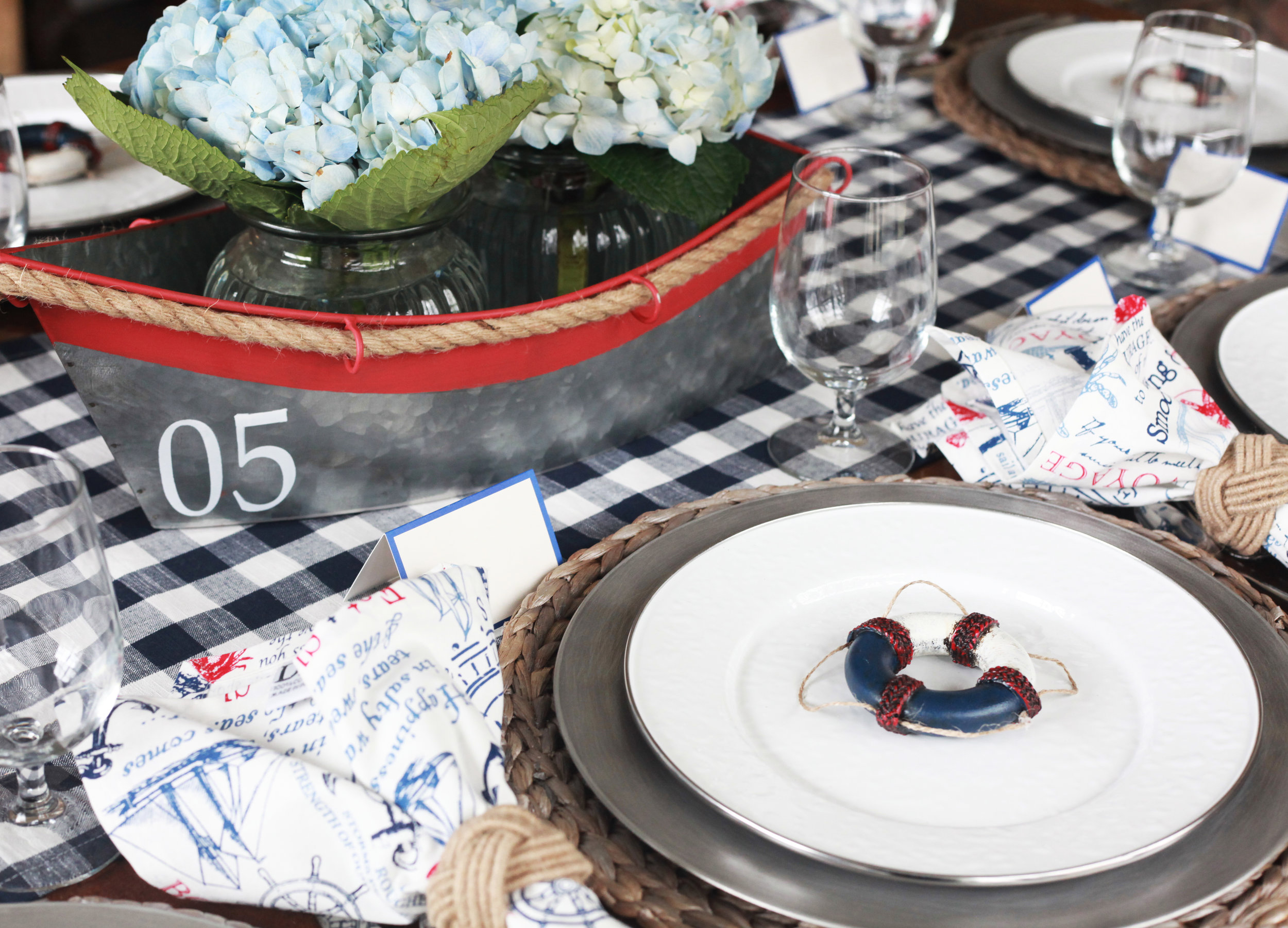 Sail the Seas - Tablescape Includes:Blue and white checkered gingham table runner, silver hued rattan charger, platinum patina charger, plate, Nautical notes printed napkin, knot napkin ring, silver rimmed enamel plate, blue rimmed place card, buoy plate accessory$14.99 per tablescapeLet your dreams set sail with this dreamy table for the captain in your life! The napkin is printed with quotes perfect for any sailor! Bon Voyage!