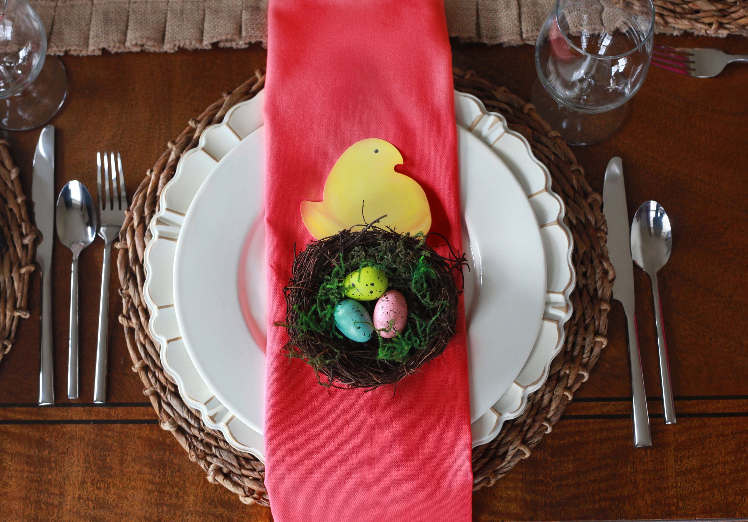 Eggstravaganza - Tablescape Includes:Burlap table runner, rattan charger, gold rimmed charger, plate, solid coral napkin, gold napkin ring, off white enamel plate, Peeps chick place card, nest plate accessory.$14.99 per tablescapeThis charming Easter/spring table is sure to get your party hopping! The vibrant coral colored napkins with gold accents are just enough to make your table shine for spring!