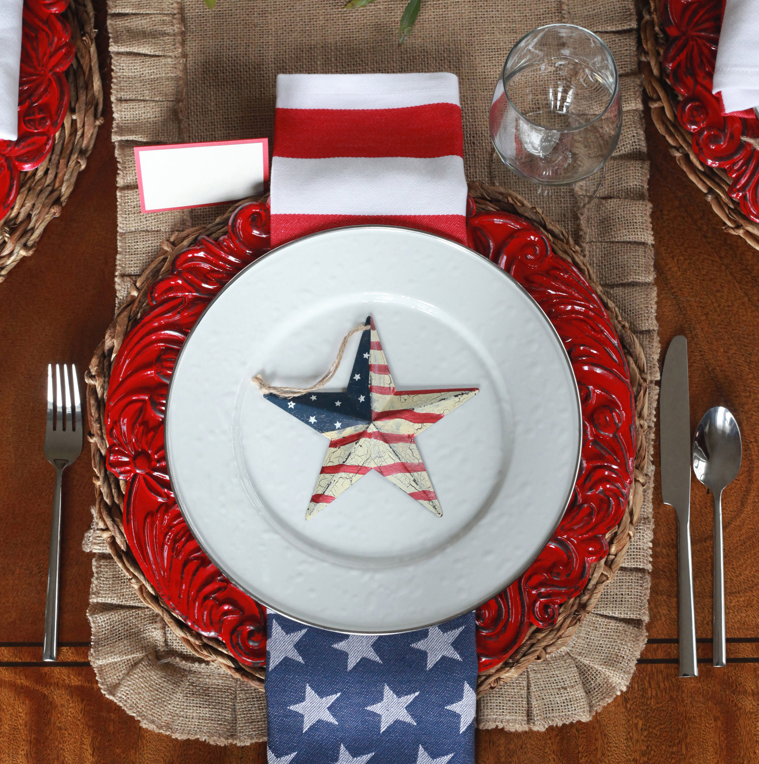 Stars and Stripes - Tablescape Includes:Burlap table runner, rattan charger, plate,  vibrant red charger, stars and stripes napkin, silver rimmed plate, star table accessory, red rimmed place card.$14.99 per TablescapeOur Stars and Stripes tablescape with launch your patriotic party as you celebrate with family and friends! Just add the fireworks to end with a bang!