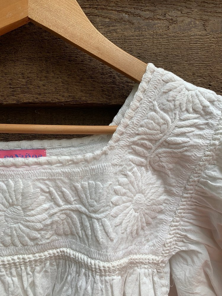 This Sophie blouse is made specially for Las Niñas Textiles. It is hand-embroidered, hand-smocked and hand-sewn by Magdalena's family, the various members creating various parts. We have worked together since 2004.