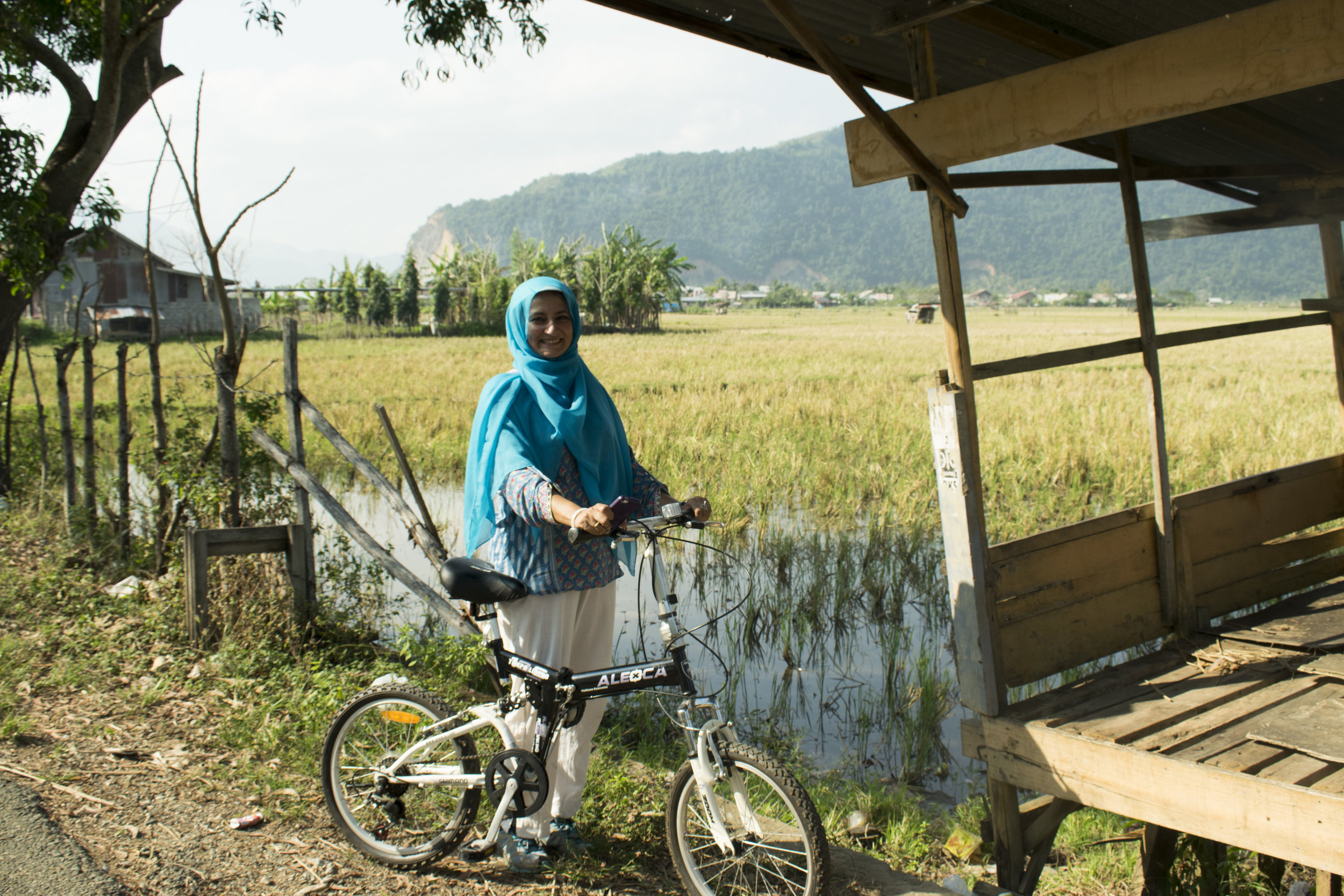 Dr. Aslam parked near a marsh on her bike ride in Aceh with 'Women on Wheels.'