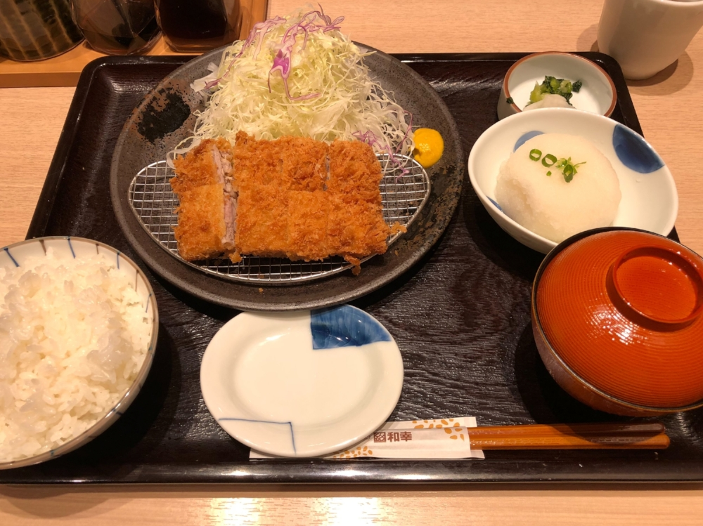 A set meal from Wakou. Tonkatsu on-top of a wire net, Served with chopped raw cabbage, rice, miso soup, grated radish, and pickles on the side.