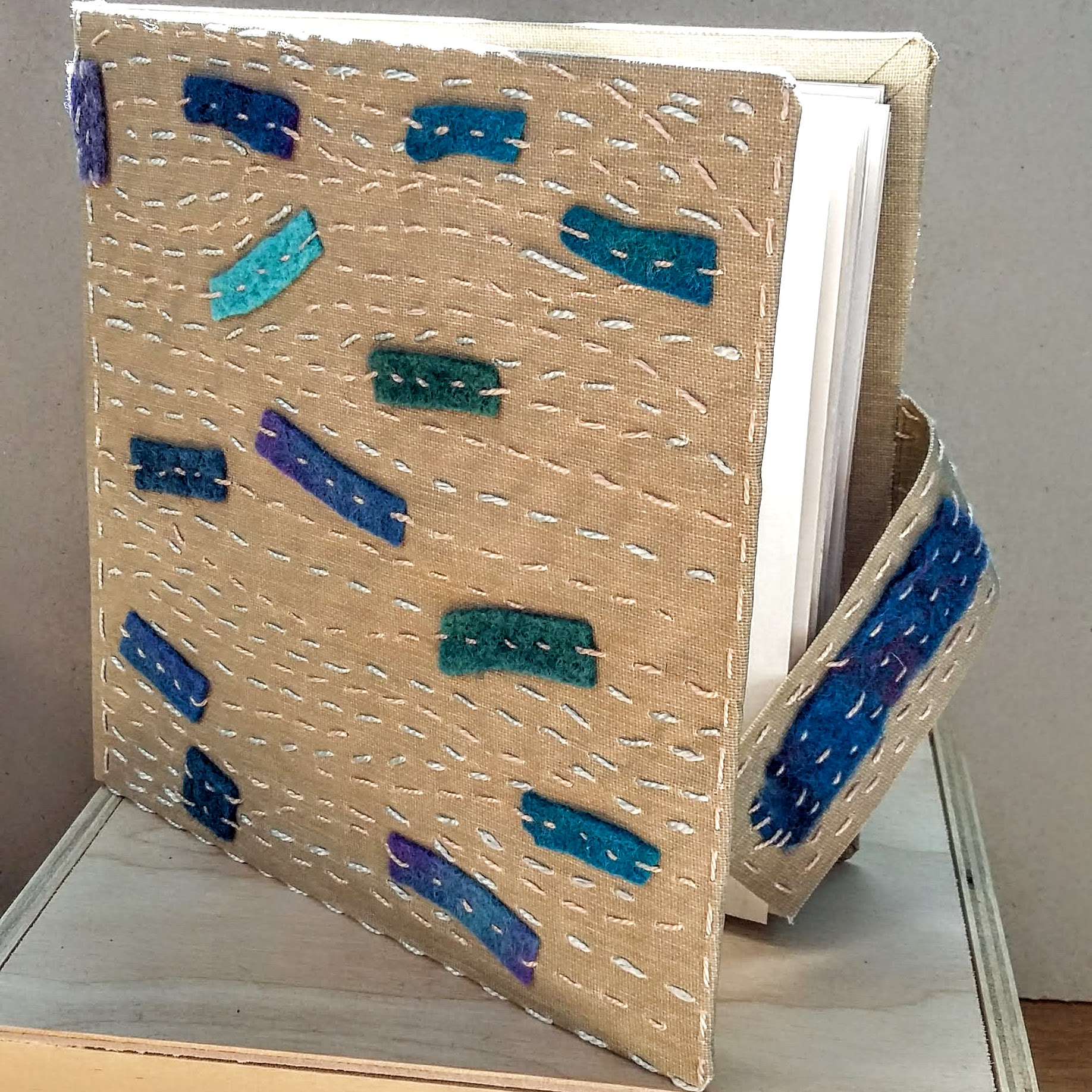 Hand stitched bookcloth Book, with magnet closure. 15.5 x 15.5 cm. 100 sides, 50 pages. £45 plus p&p