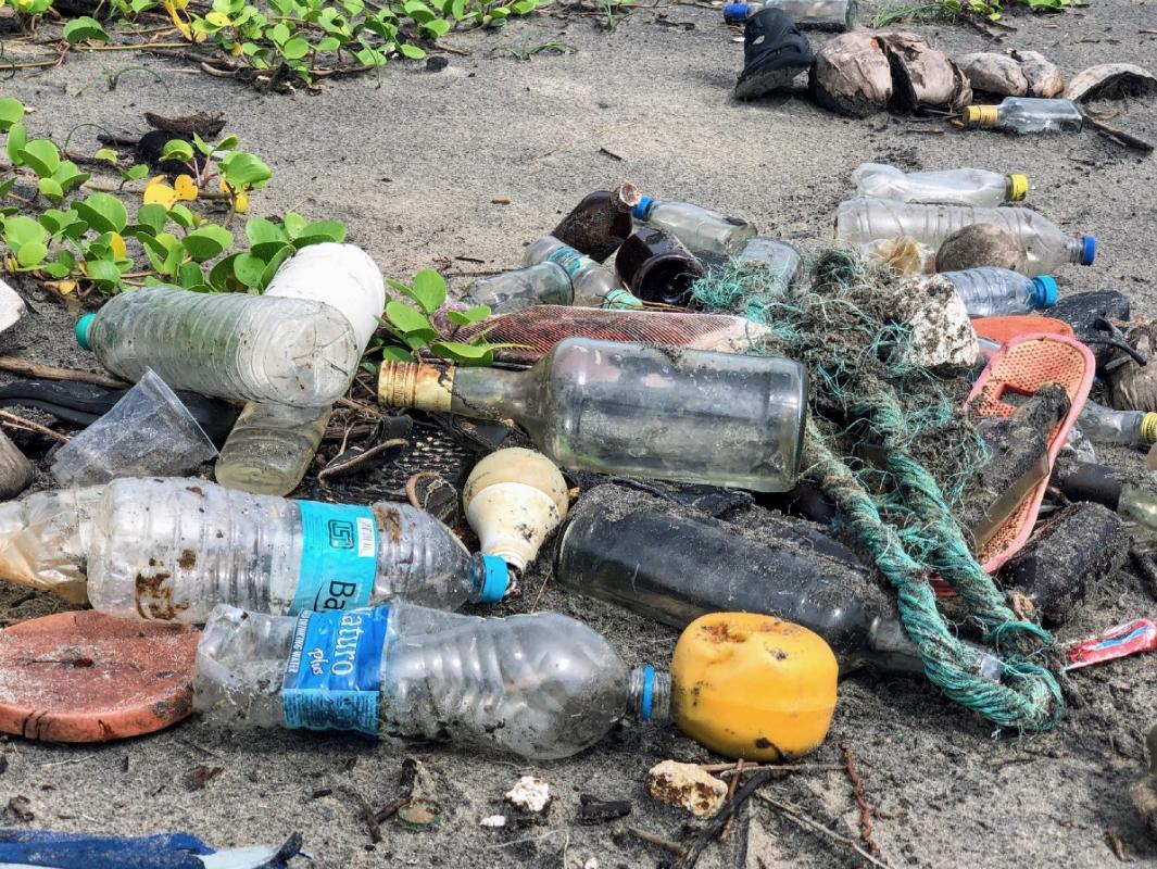 """assorted garbage bottles on sandy surface"" by  John Cameron  on  Unsplash"