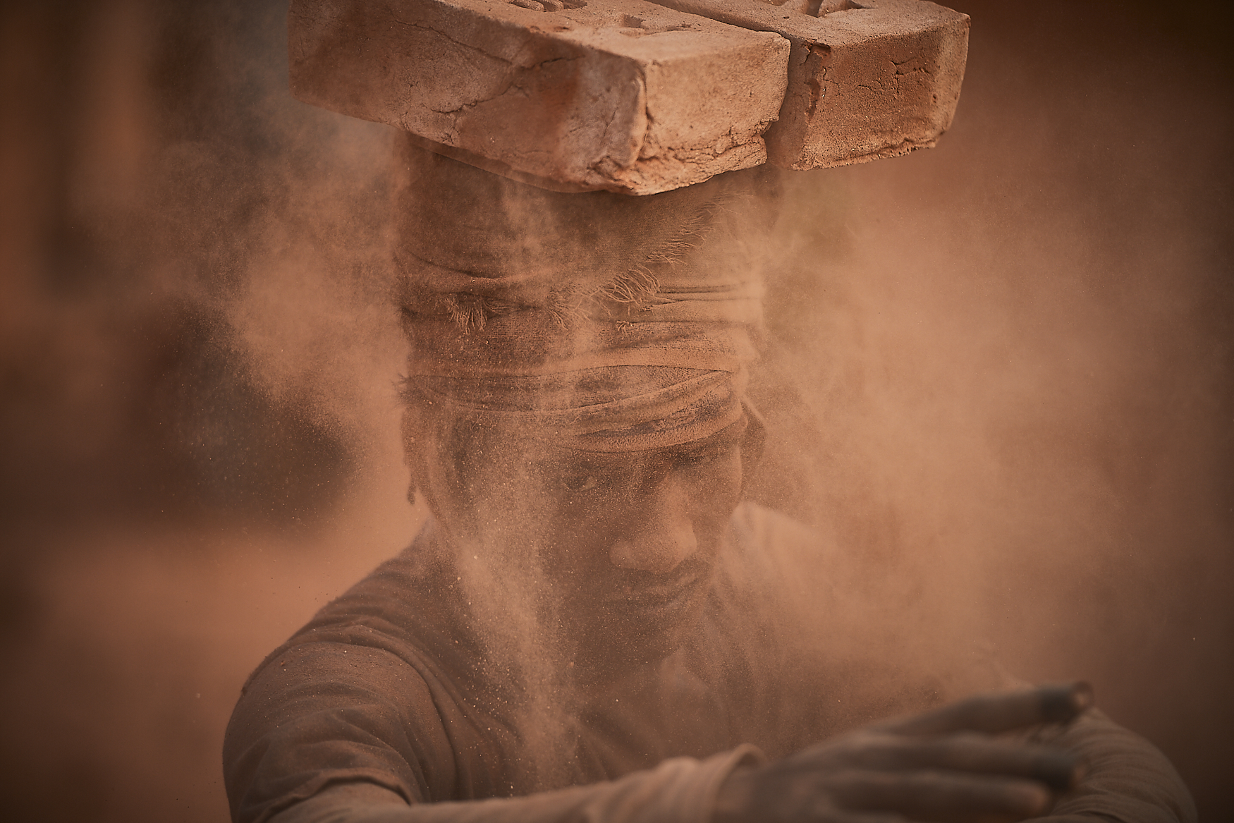 worker removing baked bricks from the kiln