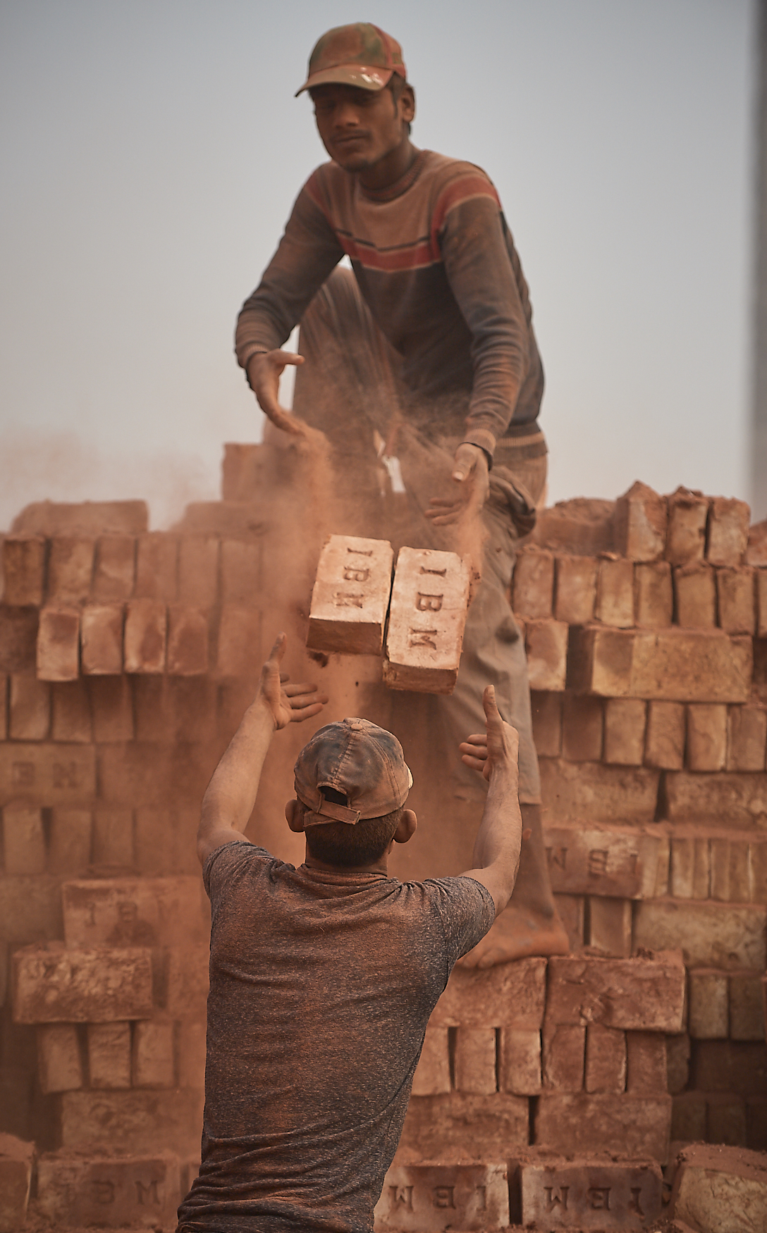 workers stacking dry bricks for baking