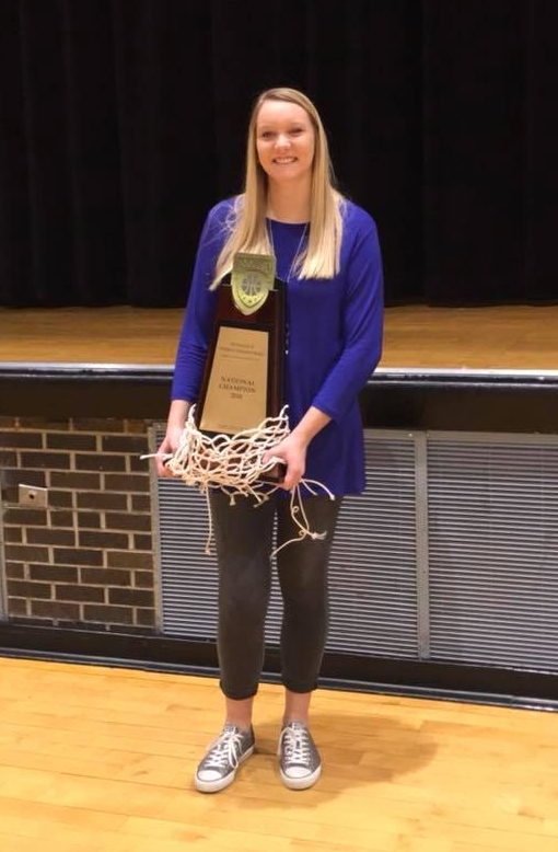 Jill Ricke, SFLS class of 2012, holds the 2018 NAIA Division II National Championship trophy, won for the first time in school history by Dakota Wesleyan University's women's basketball team.