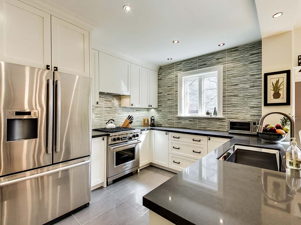 Kitchen area with stainless steel appliances and marble countertops