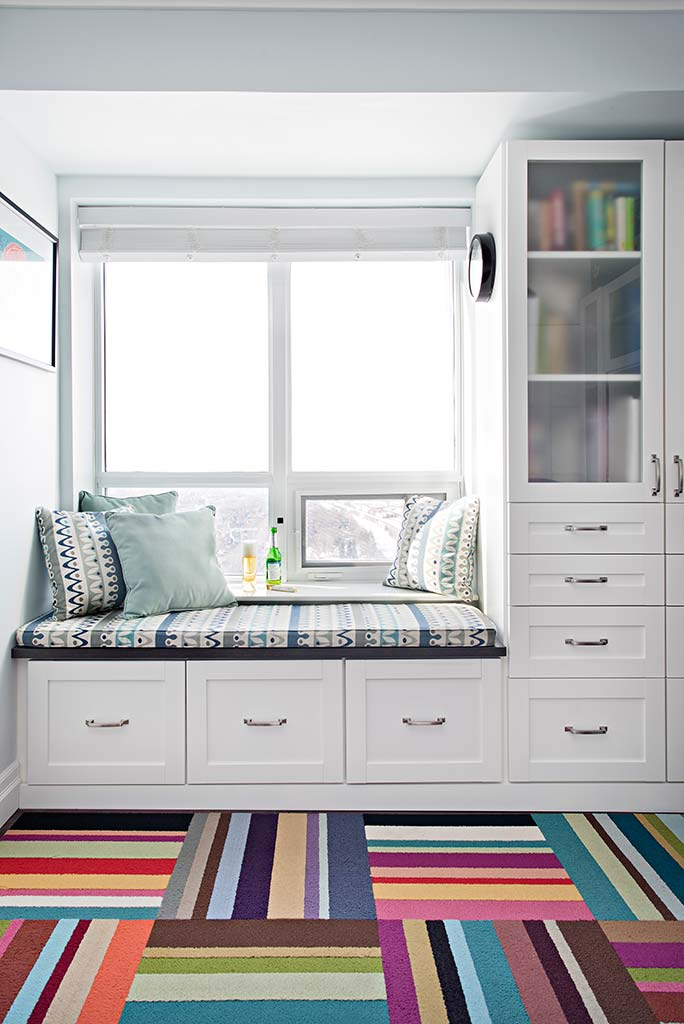 Vibrant carpeting with storage cabinets and window view