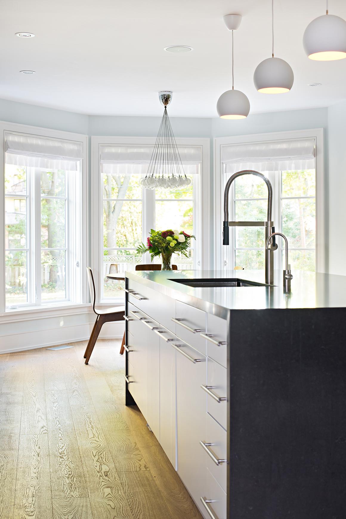 White oak wide plank flooring; modern statement pendants over island and breakfast nook by Four Blocks South interior design