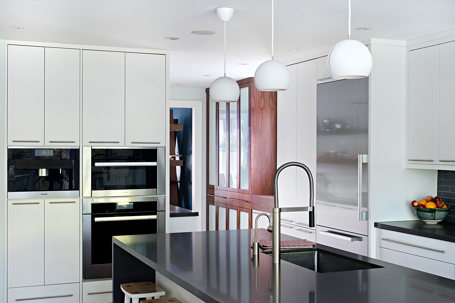 Modern white kitchen with walnut custom cabinetry by Four Blocks South residential interior design