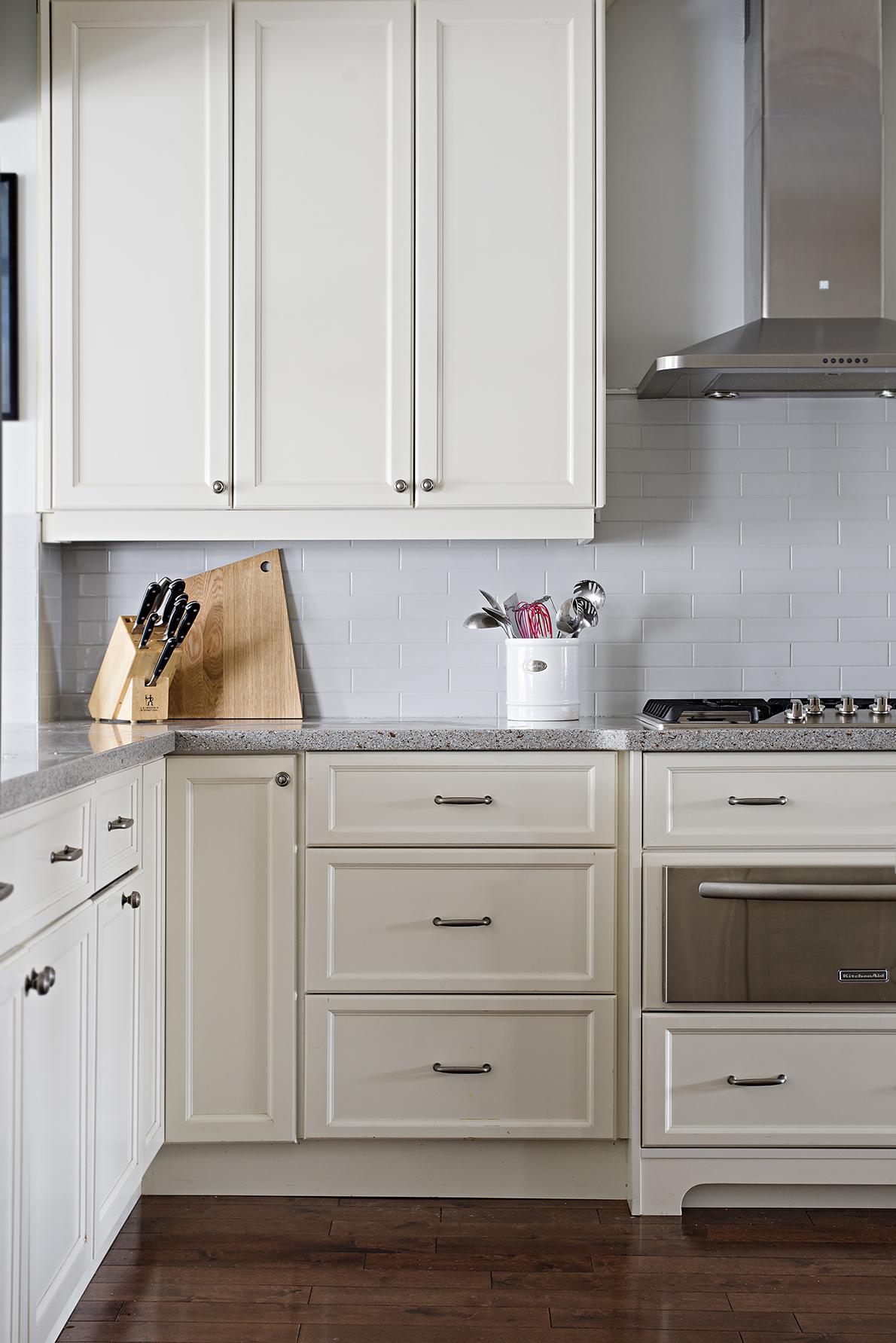 Kitchen with wood flooring, white cabinets and tiled backsplash