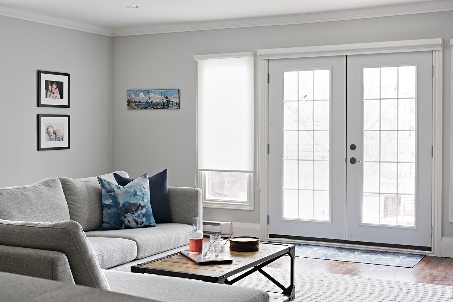 Bright living room area with large couch and french doors