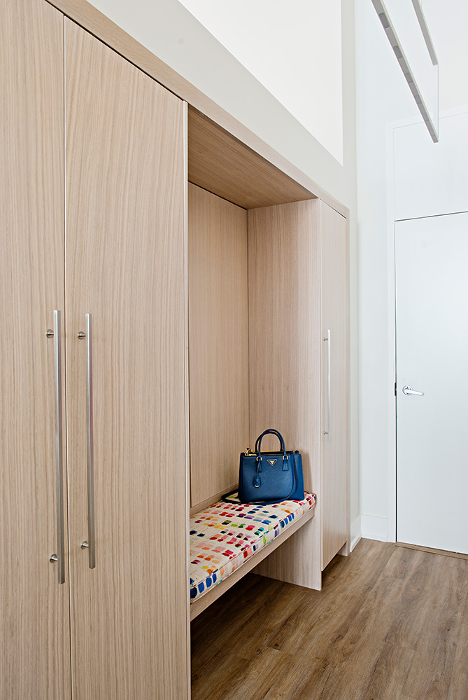 Custom white oak cabinetry and bench provide a sophisticated entry with lots of hidden storage.