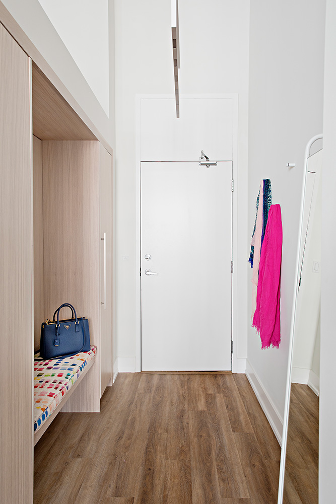A low profile overhead light illuminates this stunning entryway with custom white oak closets and bench.