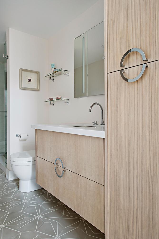 Geometric cement tiles and custom white oak vanity make for an elegant and feminine bathroom.
