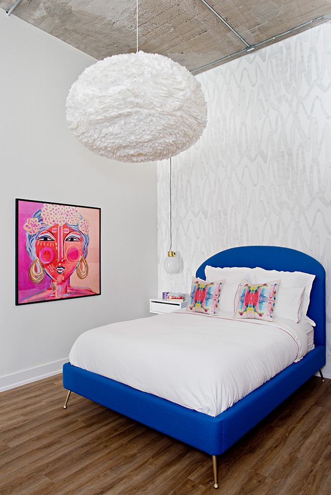 Textured feather pendant contrast beautifully with the exposed industrial ceiling. Pops of cobalt fushia in the custom bed and fuchsia artwork add drama to this girly bedroom.