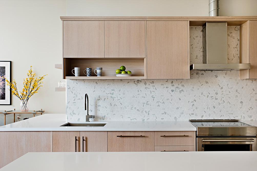 Mosaic tile cararra marble kitchen backsplash with white oak custom cabinets and white quartz countertops.