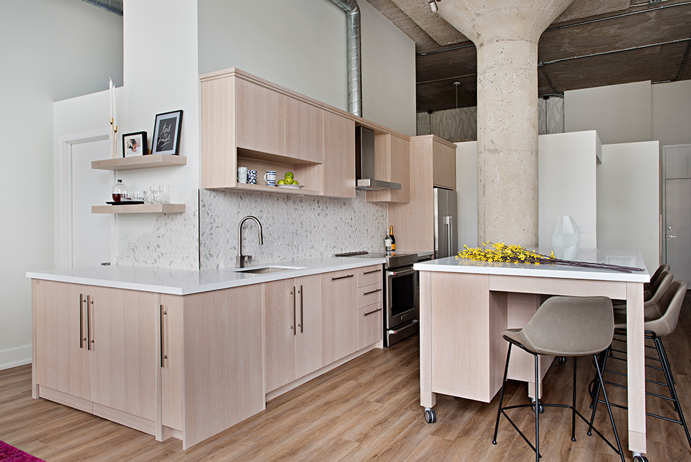 Hidden laundry machines at the end of the kitchen and moveable island function as a bar areas for parties in this white oak loft kitchen.