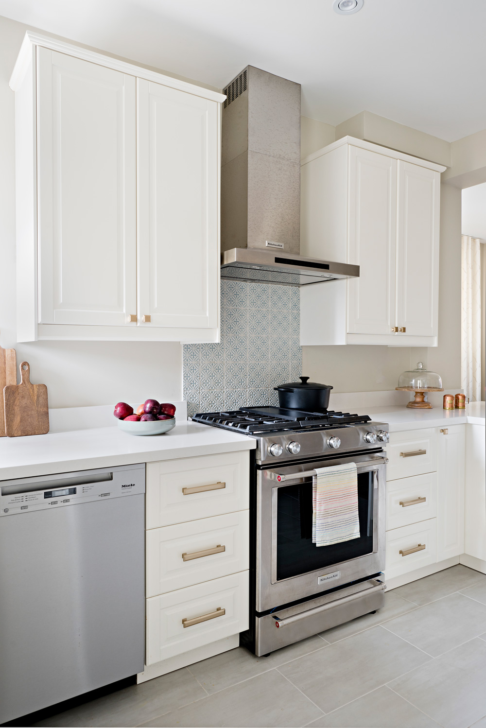 Creamy white kitchen cabinets with brass hardware. Stove with blue accent tile backsplash.