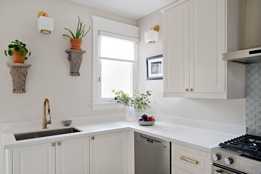 Restoration Hardware corbels above sink. White kitchen cabinets and brass accents.