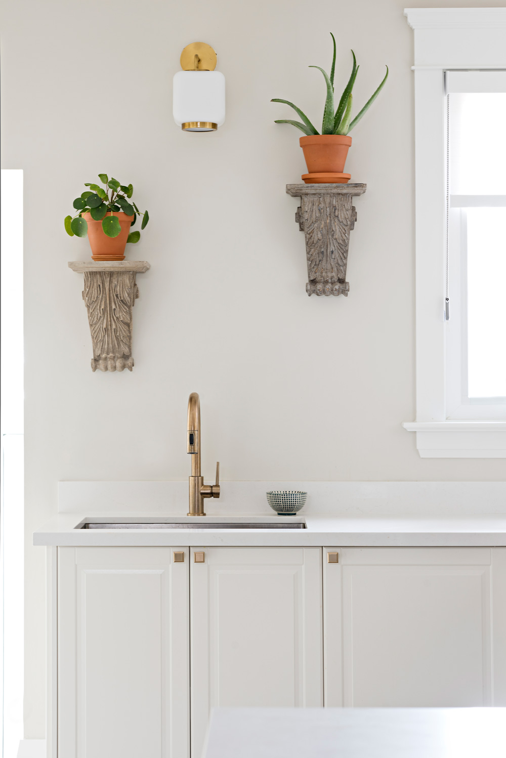 Staggered wall mounted corbels with plants above kitchen sink with brass faucet, cabinet knobs and sconces.