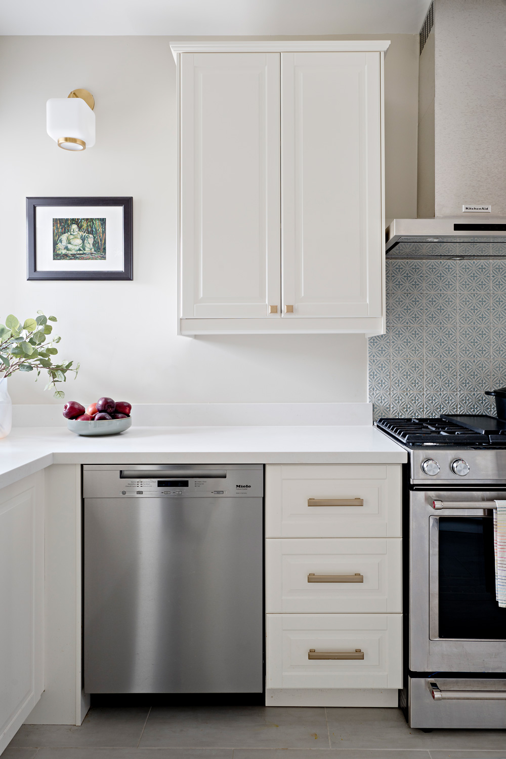 Stainless steel appliances and brass accents, mixed metals in a creamy white kitchen.
