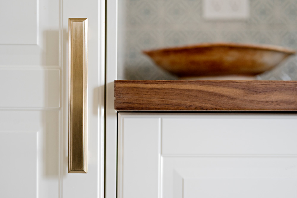 Close-up of brass kitchen cabinet pull on white Bodbyn cabinet fronts.