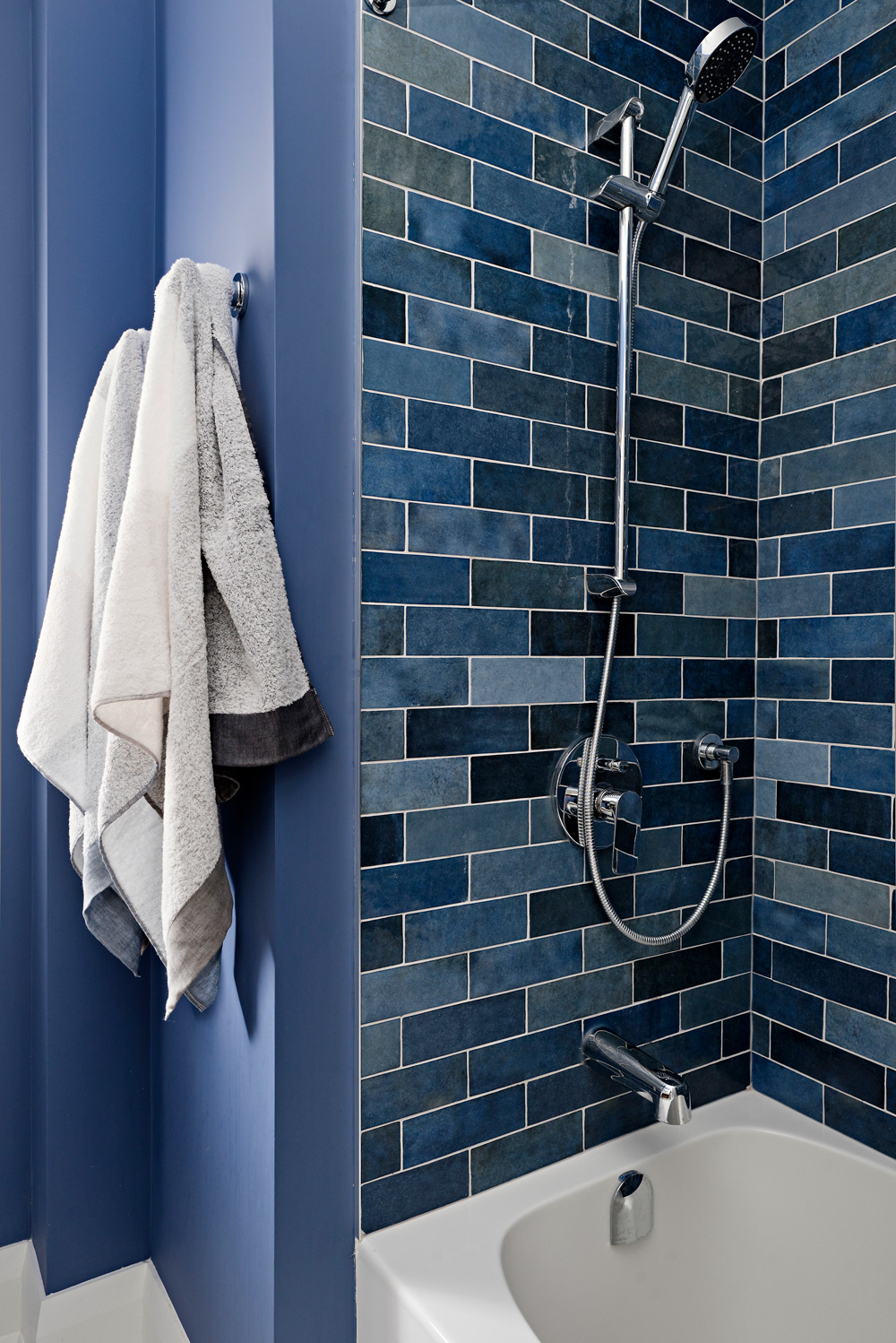 Blue accent tiles in family bathroom tub surround.