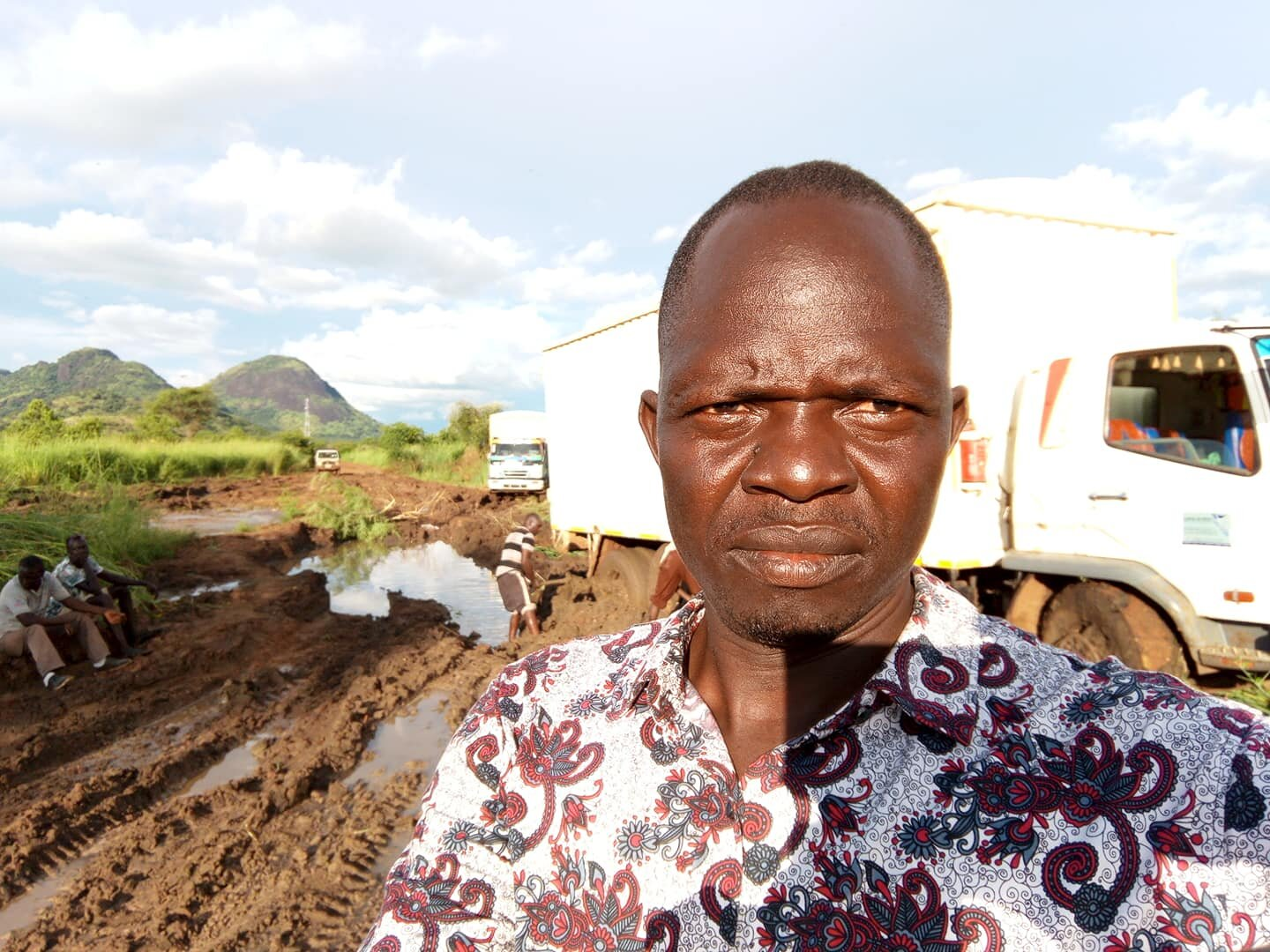 Peter Lomago with food trucks stuck in the mud in South Sudan