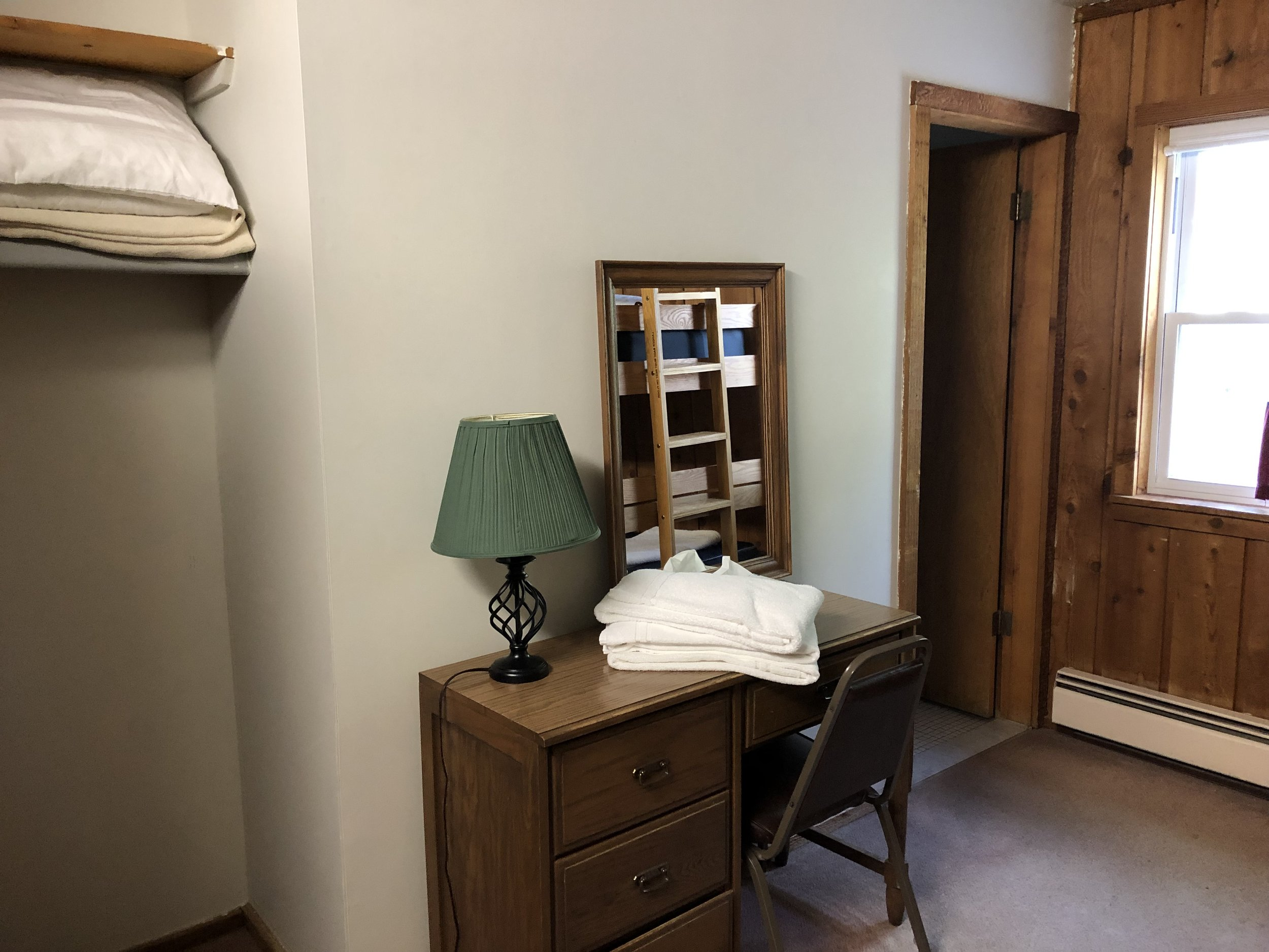 Room 212 - Desk with mirror and closet area for hanging clothes.