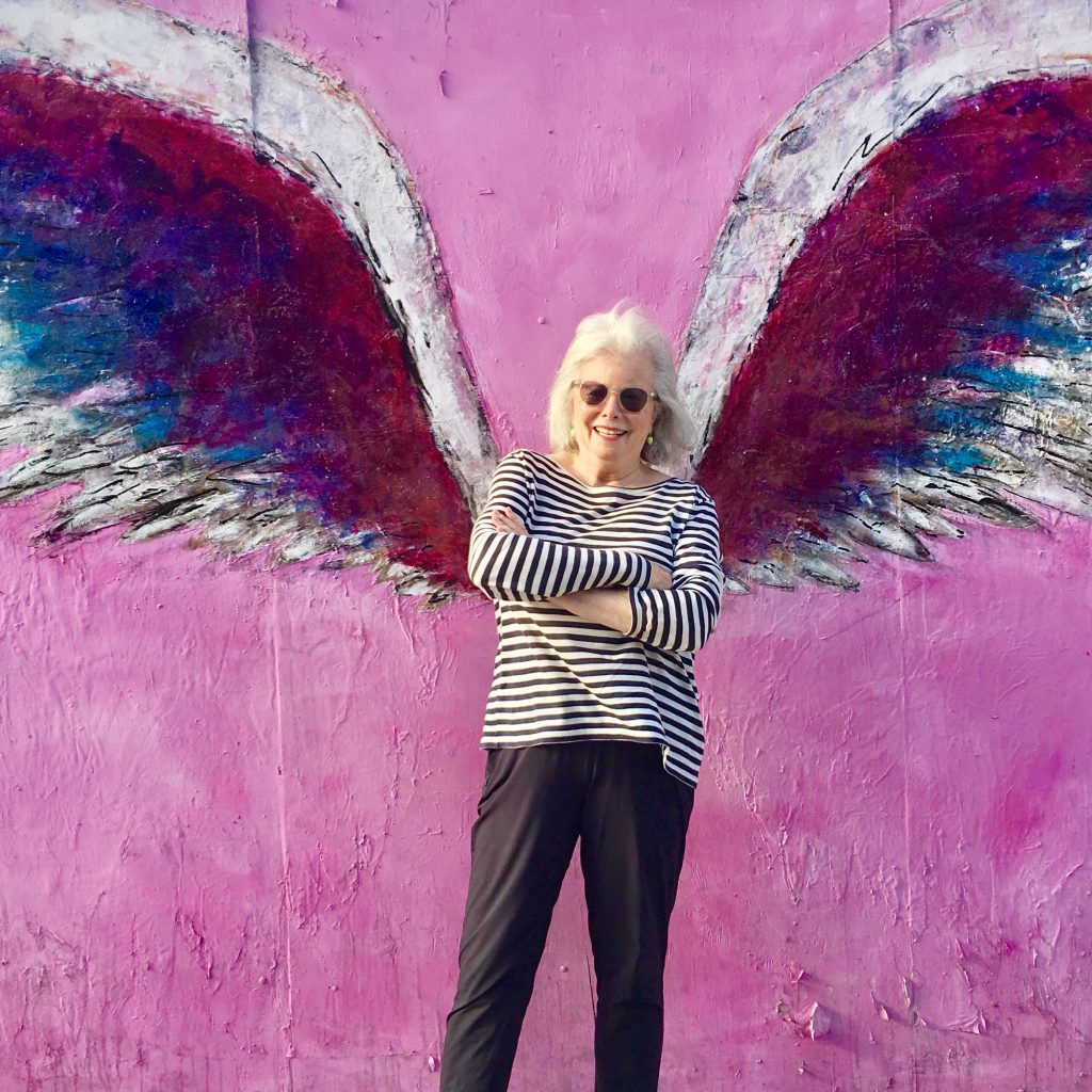 Sandra standing in front of angel painting.