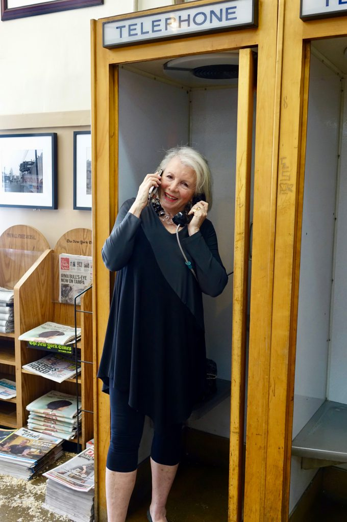 Sandra in Phone booth with iPhone