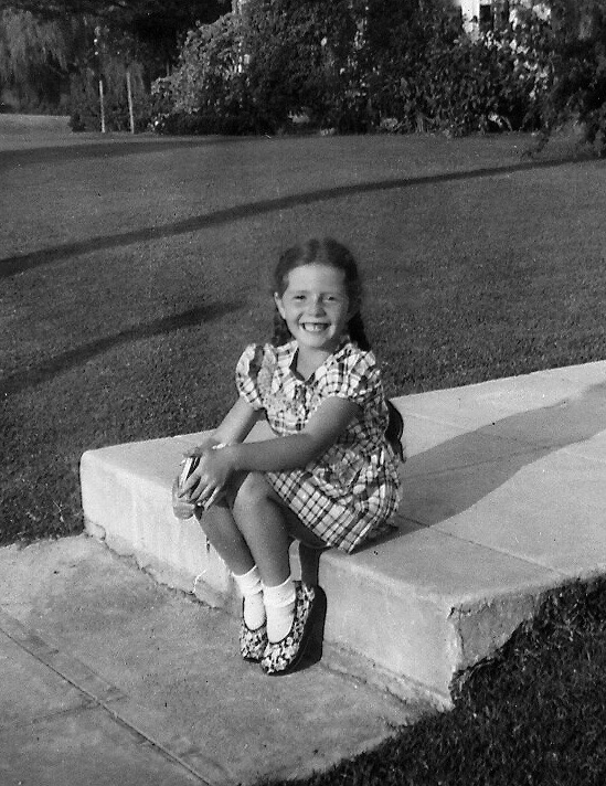 Me as a young girl sitting on a step