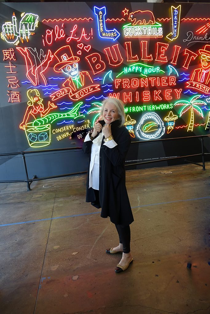 In front of the neon sign entrance to Grand Central Market in Los Angeles.