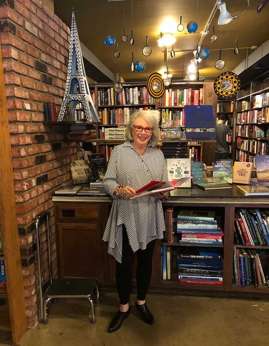Sandra standing and reading at The Last Bookstore