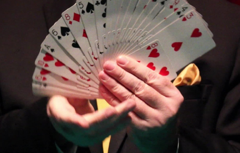 A g=magicians holding a hand of cards. Notice some are high and some are lower in his hands.