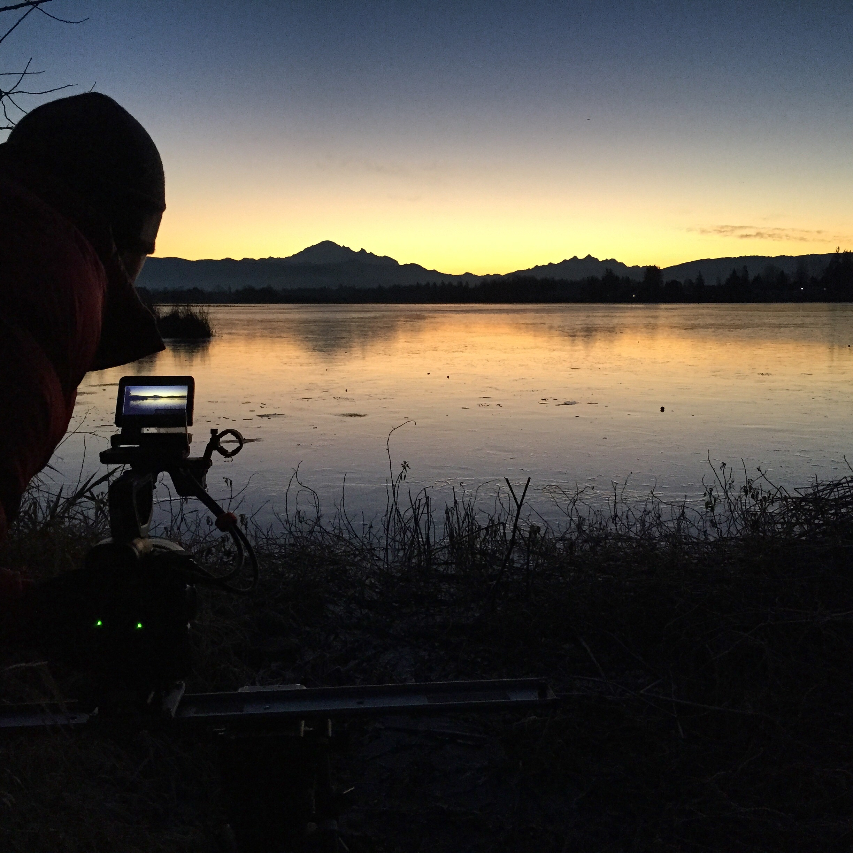 Film crew on frozen lake at sunrise