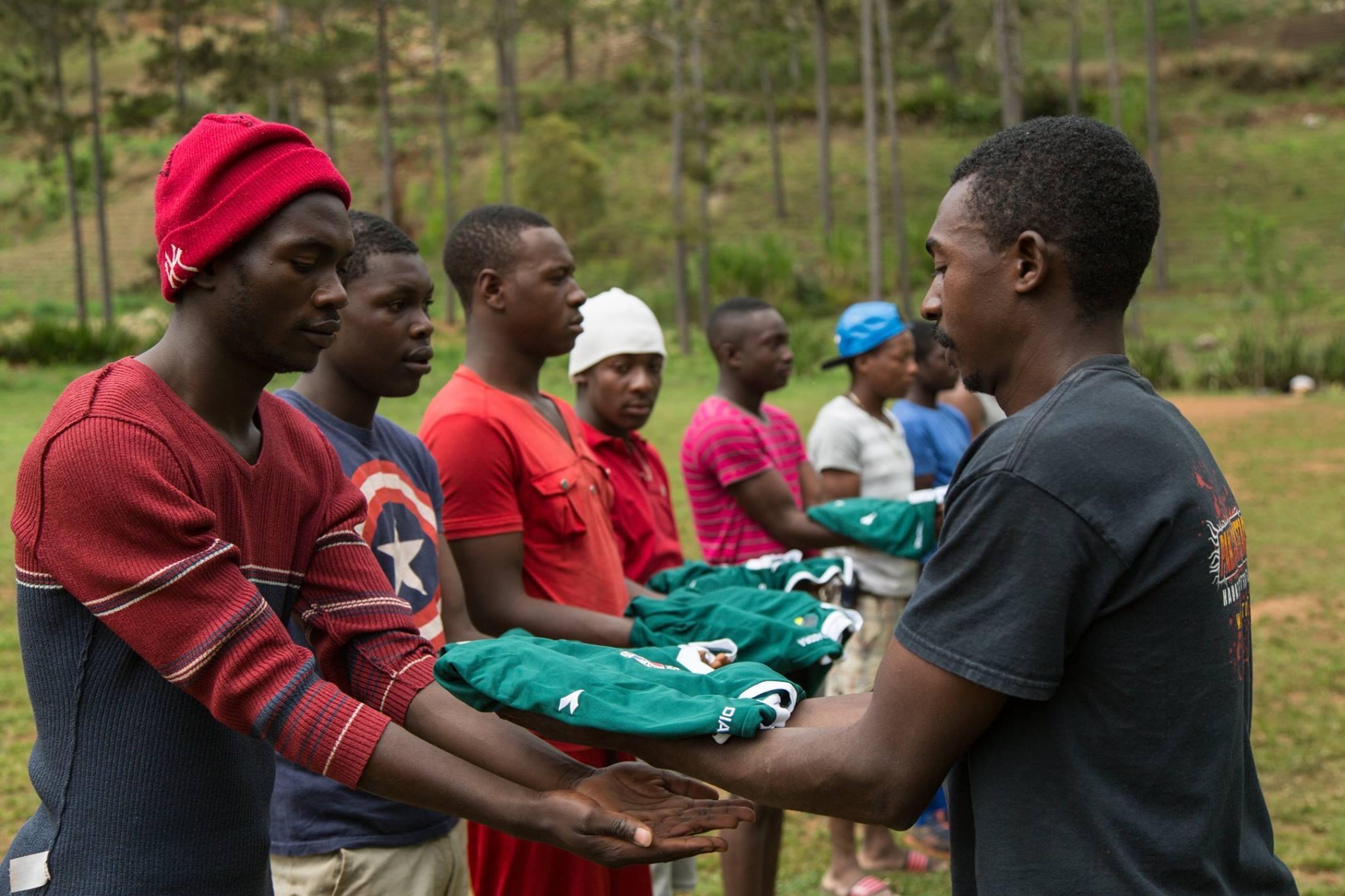 Haitian men being given soccer jerseys in Boukan Chat, Haiti